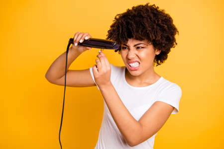 Close up photo beautiful amazing she her dark skin lady curler hands suffering hair curls not making straight rage outraged wear casual white t-shirt isolated yellow bright vibrant vivid background