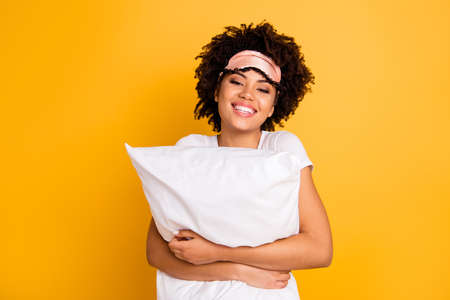 Close up photo beautiful amazing she her dark skin lady hand hug embrace pillow great weekend awakening wear sleep mask casual white t-shirt isolated yellow bright vibrant vivid background