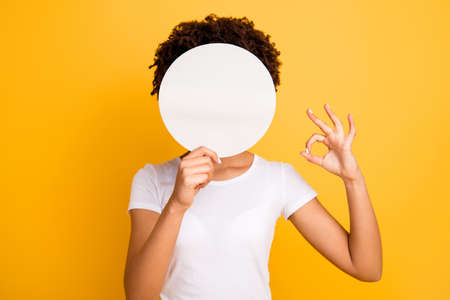 Close up photo beautiful amazing she her dark skin lady hiding face okey symbol fingers round circle paper unrecognized opinion wear casual white t-shirt isolated yellow bright vibrant background