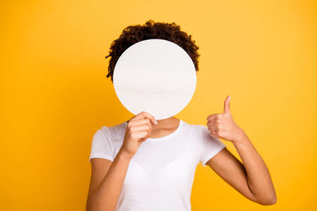 Close up photo beautiful amazing she her dark skin lady hiding face thumb up round circle placard do not want be recognized wear casual white t-shirt isolated yellow bright vibrant vivid background Foto de archivo - 117893131