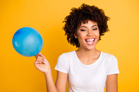 Close up photo beautiful amazing she her dark skin lady hold air balloon hands arms excited funky voice breath in helium wear casual white t-shirt isolated yellow bright vibrant vivid background