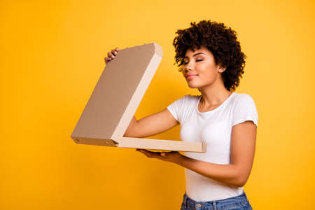 Portrait of her she nice cute lovely pretty beautiful cheerful dreamy wavy-haired lady holding in hands carton pizza box smelling isolated over bright vivid shine background Stock Photo