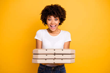 Portrait of her she nice cute lovely charming attractive beautiful cheerful wavy-haired lady holding in hands showing three carton pizza boxes isolated over bright vivid shine background Stock Photo