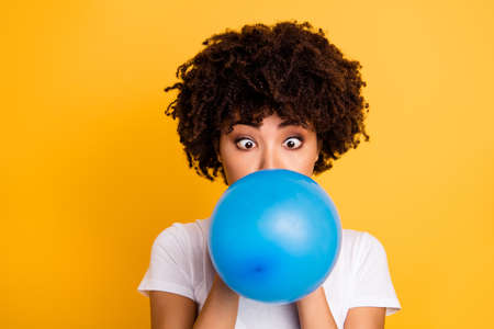 Close up photo beautiful amazing she her dark skin lady hold air balloon surprised stupor hiding face big crossed eyes wear casual white t-shirt isolated yellow bright vibrant vivid background