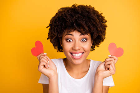 Close up photo beautiful amazing she her dark skin lady sweet arranging best date boyfriend paper hearts shape figure postcard wear casual white t-shirt isolated yellow bright vibrant background