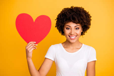 Close up photo beautiful amazing she her dark skin lady showing big paper card heart shape figure form lovely date invitation wear casual white t-shirt isolated yellow bright vibrant background 스톡 콘텐츠