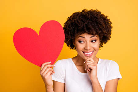 Close up photo beautiful amazing she her dark skin lady hand chin great idea big paper card heart shape figure form date invitation wear casual white t-shirt isolated yellow bright vibrant background