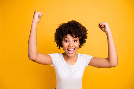 Close up photo beautiful amazing she her dark skin lady not believe yelling glad hands arms fists raised great big win competition wear casual white t-shirt isolated yellow bright vibrant background