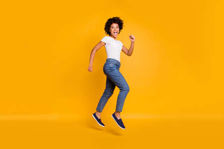 Full length body size side profile photo jumping high beautiful she her lady rushing shopping big shopper mall store wearing casual jeans denim white t-shirt clothes isolated yellow background