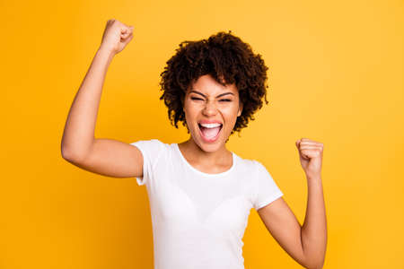 Close up photo beautiful amazing she her dark skin lady yelling loud glad hands arms fists raised great big win competition wear casual white t-shirt isolated yellow bright vibrant vivid background