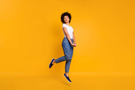 Full length body size side profile photo jumping high beautiful she her lady sending kisses graceful hands arms together wearing casual jeans denim white t-shirt clothes isolated yellow background