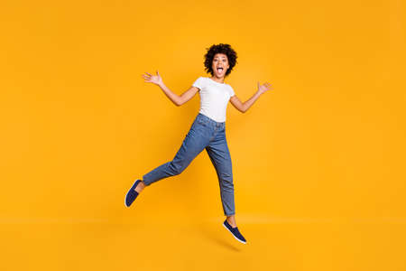 Full length body size photo jumping high beautiful she her lady like comedian actor playful active energetic wearing casual jeans denim white t-shirt clothes isolated yellow background 版權商用圖片
