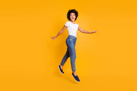 Full length body size side profile photo jumping high beautiful she her lady yelling rushing shopping low prices amazed wearing casual jeans denim white t-shirt clothes isolated yellow background