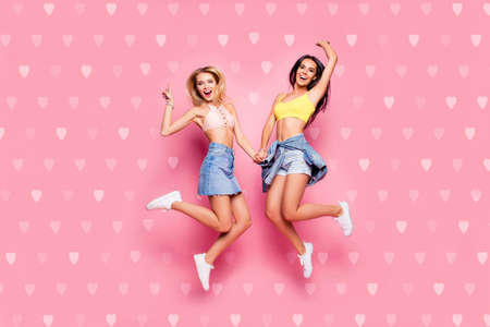 Life is cool Full length body size view of beautiful attractive funny cheerful careless girls in casual trendy outfit white shoes jumping up holding hands isolated on pastel pink background 免版税图像