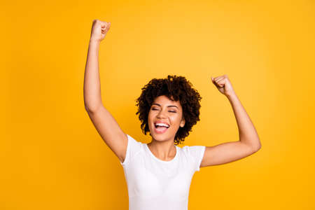 Close up photo cheerful beautiful amazing she her dark skin lady not believe gladness yelling hands arms raised up great big win wear casual white t-shirt isolated yellow bright vibrant background Stock fotó