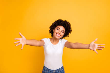 Close up photo cheerful beautiful amazing she her dark skin lady spread hands arms come here to us calling in hugs sweetheart wear casual white t-shirt isolated yellow bright vibrant background Фото со стока