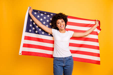 Close up photo beautiful amazing she her dark skin lady hands arms hold american flag festive mood 4th of july wearing casual jeans denim white t-shirt isolated yellow bright vibrant background