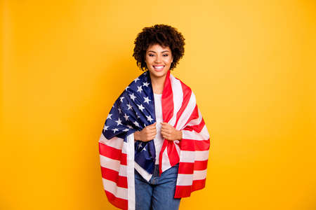 Close up photo beautiful amazing she her dark skin lady hands arms hold american flag best country party 4th of july wearing casual jeans denim white t-shirt isolated yellow bright vibrant background