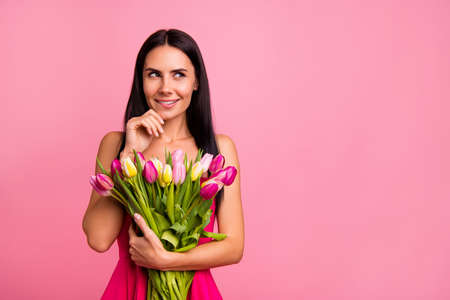 Portrait of her she nice-looking cute attractive lovely pretty fascinating charming cheerful brunette lady holding in hands colorful flowers florist biting lips isolated on pink pastel background