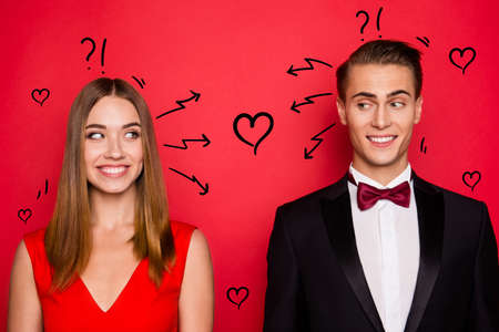 Closr-up portrait of two nice chic lovely attractive imposing cheerful funny flirty people wearing dress and bow tux looking at each other thinking isolated over bright vivid shine red background