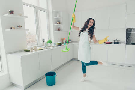 FUll length body size photo beautiful busy nice duties she her lady indoors dancing with washing supplies floor housemaid wear jeans denim casual t-shirt covered by cute apron bright light kitchen