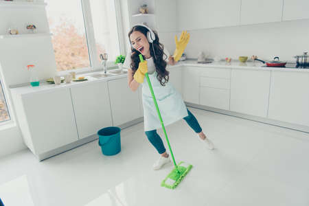 Full length body size portrait of her she nice beautiful lovely charming cheerful wavy-haired house-wife using broom like mic having fun in modern light white interior indoors