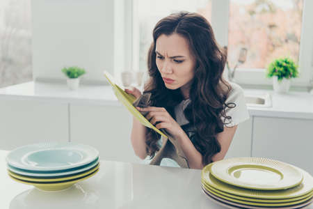 Portrait of her she nice cute beautiful concentrated unsatisfied wavy-haired house-wife polishing plates piles on table in modern light white interior indoors Banque d'images