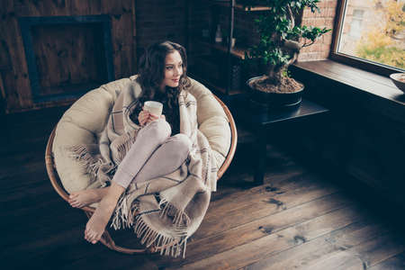 Close up photo sweet beautiful brunette she her lady calm homey living room morning relaxing hot beverage covered blanket wearing domestic home apparel clothes outfit sit comfy arm-chair