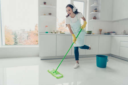 Full length body size side profile photo beautiful hardworking duties she her lady house dancing singing ear flaps on head wear jeans denim casual t-shirt covered cute apron bright light kitchen