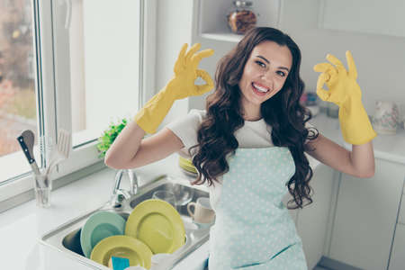 Portrait of her she nice adorable winsome charming attractive beautiful cheerful optimistic wavy-haired house-wife showing two double ok-sign in yellow gloves in modern light white interior