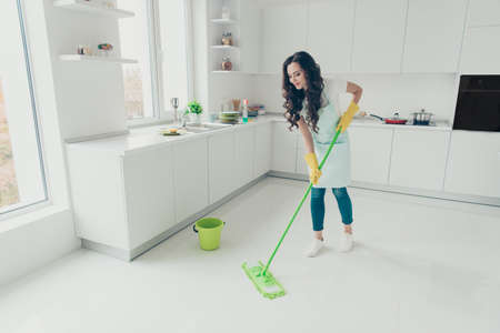 FUll length body size photo beautiful busy nice duties she her lady housewife wash white floor carefully not hurry housemaid wear jeans denim casual t-shirt covered by cute apron bright light kitchen