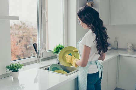 Profile side view portrait of her she nice charming lovely attractive beautiful cheerful wavy-haired house-wife washing green plates in yellow gloves in modern light white interior Stockfoto - 118007040