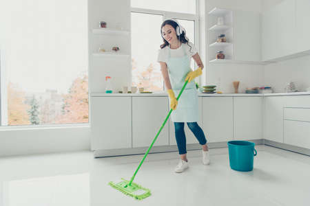 Full length body size side profile photo beautiful attentive hardworking nice pleasant duties she her lady house ear flaps head wear jeans denim casual t-shirt covered cute apron bright light kitchen