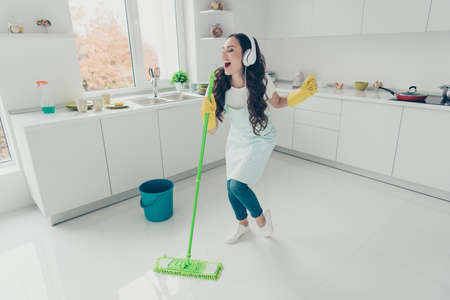 Full length body size photo beautiful attentive hardworking pleasant duties she her lady house ear flaps head playlist audio wear jeans denim casual t-shirt covered cute apron bright light kitchen Reklamní fotografie