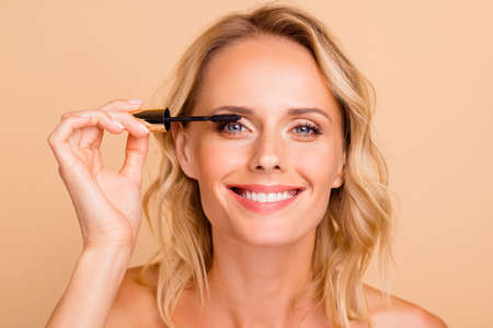 Close-up portrait of trendy modern nice cheery wavy-haired lady with perfect pure clean clear fresh smooth flawless shine skin applying mascara brush on eye lashes isolated on beige background Imagens