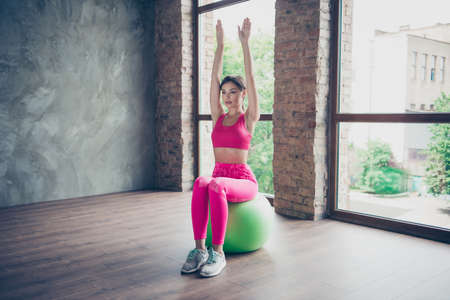 Portrait of her she nice graceful beautiful attractive thin perfect line form shape lady wearing pink top look outfit sitting on green fit-ball raising hands up in modern loft industrial interior
