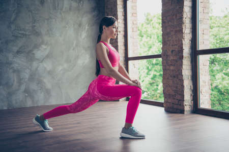 Profile side view of nice strong beautiful attractive graceful thin sportive lady doing one leg situps in modern loft industrial interior style indoors