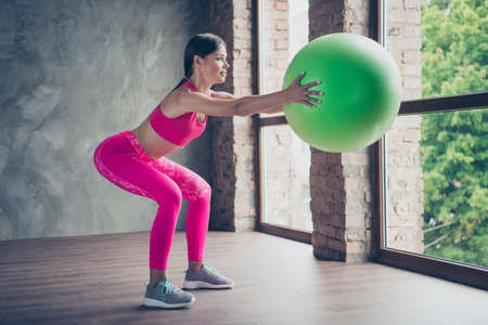 Profile side view portrait of her she nice cute beautiful attractive charming thin lady wearing pink outfit look holding in hand green fit-ball doing sit-ups in modern loft industrial interior Banco de Imagens