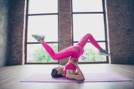 Profile side view of her she nice attractive sportive thin perfect shape form lady wearing pink clothes top doing acrobatics moves position in modern loft industrial interior style Banco de Imagens