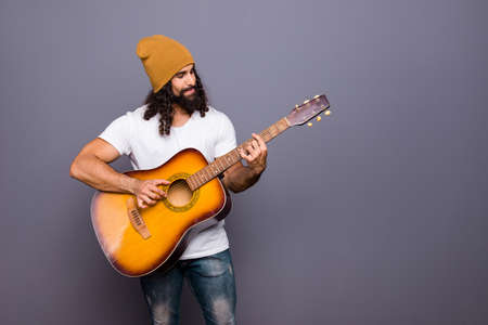 Portrait of nice handsome attractive cheerful confident wavy-haired guy playing guitar hit pop rock composition isolated over gray pastel background.
