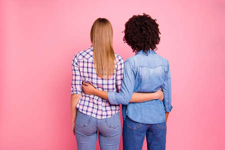 Close up back rear behind view photo two mindless diversity she her ladies hugging incognito not show faces wear casual jeans denim checkered shirt clothes outfit isolated pink background. Stok Fotoğraf