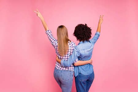Close up back rear behind view photo two mindless diversity she her ladies hugging incognito not show faces v-signing wear casual jeans denim checkered shirt clothes outfit isolated pink background.