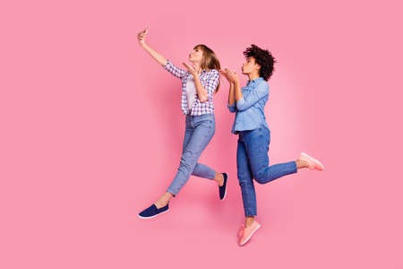 Full length body size profile side view of two person nice lovely attractive charming cheerful playful flirty girls having fun time taking making selfie isolated over pink pastel background