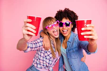 Close-up portrait of two person nice cute cool fascinating lovely attractive charming cheerful girls in casual checkered shirt giving beverage isolated over pink pastel background Standard-Bild - 119233642