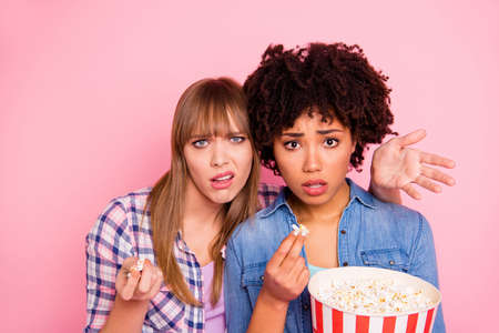 Close up photo two diversity she her ladies different race skin open mouth oh no awful film food pop corn wtf face wear casual jeans denim checkered shirt clothes outfit isolated pink background Stock fotó
