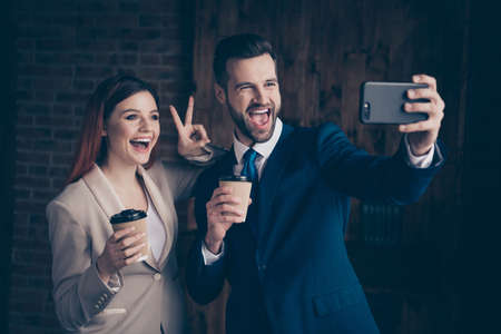Close up photo she her business lady he him his guy buddies hold hot takeaway shop beverage hands arms smart phone make take selfies show v-sign say hi stand office wearing formal wear suits Stock fotó
