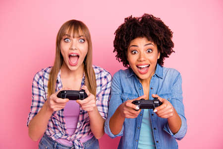 Close-up portrait of two person nice crazy fascinating lovely attractive charming cheerful excited girls in casual checkered shirt playing online having fun isolated over pink pastel background