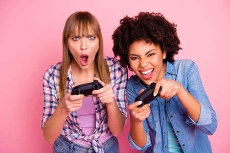 Close-up portrait of two person nice lovely attractive charming cheerful excited girls in casual checkered shirt playing online isolated over pink pastel background Stock Photo
