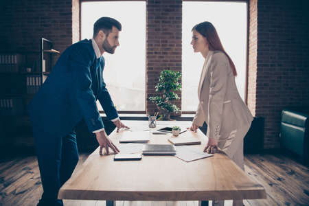 Close up photo two partners she her business lady he him his guy I will get promotion competitive mood strict look eyes who is winner concept stand office table wearing formal wear suit Banco de Imagens
