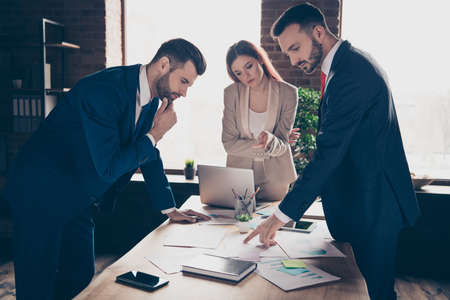 Close up photo three partners she her business lady he him his guy discuss new plan check income earnings observe future financial steps look for mistakes stand office table wearing formal wear suit